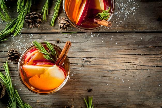 クリスマス感謝祭の飲み物秋冬カクテルグロッグホットサングリアグリューワイン-アップルローズマリーシナモンアニス古い素朴な木製のテーブルにコーンローズマリー