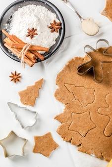 Рождественская выпечка имбирное тесто для пряников пряничные человечки звезды рождественские елки скалкой специи (корица и анис) мука на домашней кухне стол из белого мрамора