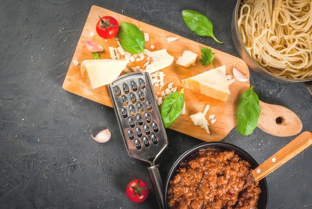 Ингредиенты итальянской кухни продукты для приготовления макаронных изделий болоньезе, процесс приготовления сварные спагетти в соусе болоньезе с базиликом, чесноком, помидорами, пармезаном