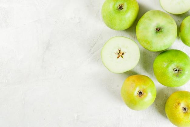 白い石のテーブル全体に緑のリンゴとカット