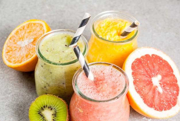 デトックスオーガニックダイエット飲料自家製トロピカルスムージー-グレーの石のテーブルに分割された瓶にキウイオレンジグレープフルーツ