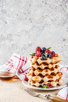 ラズベリー、ブルーベリー、シロップ、自家製の健康的な朝食のベルギーワッフル