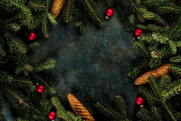 モミの木の枝、松ぼっくり、クリスマスツリーのボールとクリスマスの暗い青色の背景コピーフレーム上のスペース