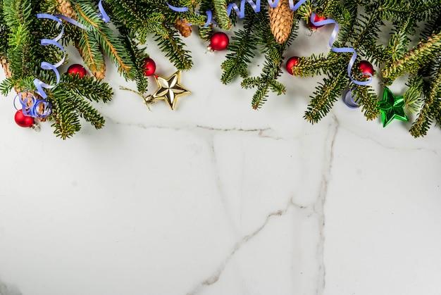 Рождественский белый фон с еловыми ветками, сосновыми шишками и елочными шарами копирует пространство над рамкой