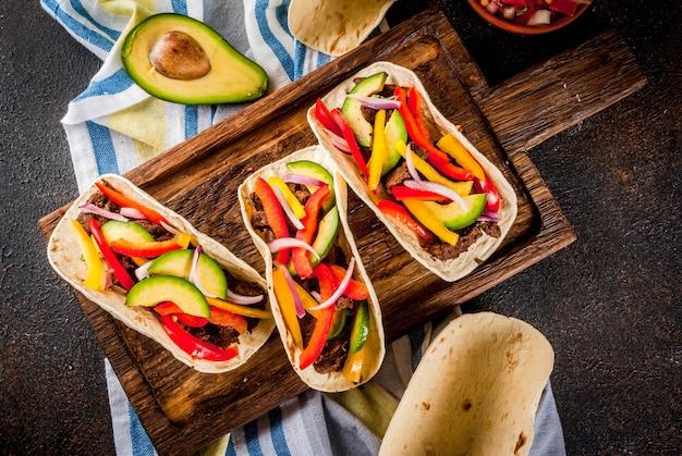 Домашние мексиканские свиные тако с овощами и сальсой, на темной ржавой столешнице
