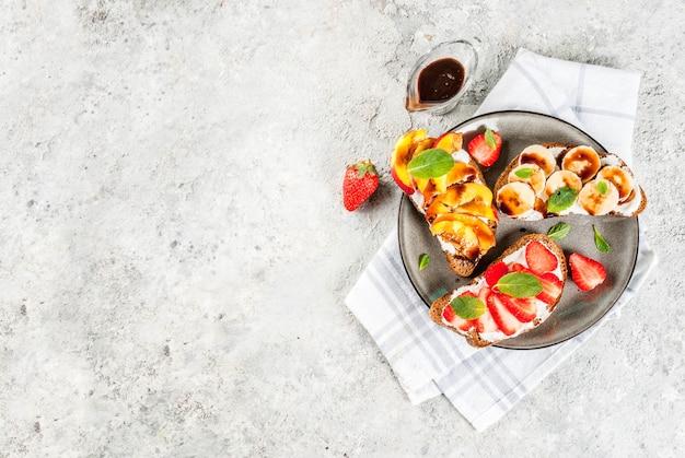 健康的な夏の朝食スナック、フルーツとベリーのライ麦トーストサンドイッチ-ストロベリー、ピーチ、バナナ-チョコレートソース、明るいコンクリート背景コピースペース