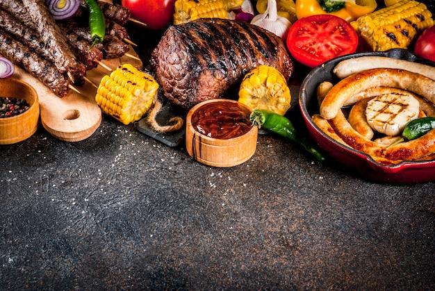 各種バーベキューフードグリル肉、バーベキューパーティーフェスト-シシカバブ、ソーセージ、焼き肉の切り身、新鮮な野菜、ソース、スパイス、コピースペースの上の暗いさびたコンクリートテーブル