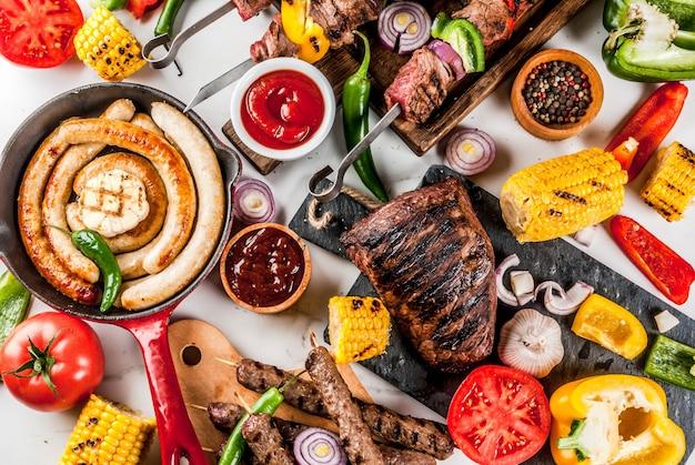 Ассорти из различных блюд барбекю, приготовленных на гриле, мясо, барбекю-вечеринка - шашлык, колбаски, филе мяса на гриле, свежие овощи, соусы, специи, поверхность из белого мрамора, над копией пространства