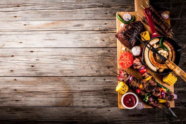 各種バーベキューフードグリル肉、バーベキューパーティーフェスト-シシカバブ、ソーセージ、焼き肉の切り身、新鮮な野菜、ソース、スパイス、コピースペースの上の古い木製の素朴なテーブルの上
