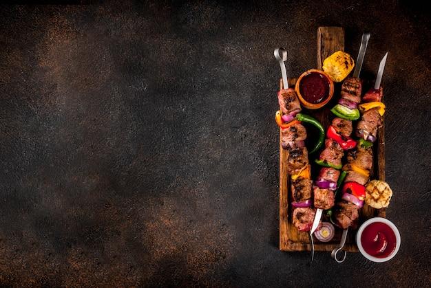 Свежий домашний шашлык из мяса на гриле с овощами и специями, с соусом барбекю и кетчупом, на темном фоне на деревянной разделочной доске над копией пространства