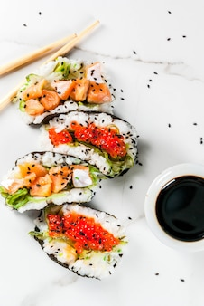 トレンドハイブリッドフード日本アジア料理ミニ寿司タコスサンドイッチサーモンハヤシワカメ大根ジンジャーレッドキャビア箸付きの白い大理石のテーブル醤油