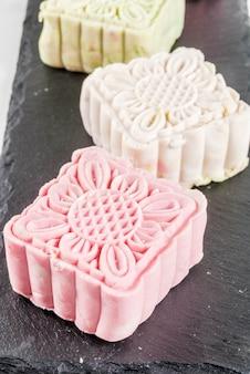 アジアの日本料理白い大理石のテーブルに伝統的な甘いデザート色とりどりの焼けない雪肌の月餅