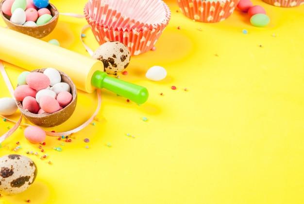 Сладкая концепция выпечки для пасхального приготовления фона с выпечкой - со взбивающей скалкой для взбивания формочек для выпечки перепелиных яиц сахарной посыпкой