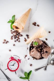 フレームの時間の目覚まし時計で、コーヒーの概念のための時間。コーヒー豆とミントの葉を添えた自家製コーヒーアイスクリーム、アイスクリームコーン、スプーン。