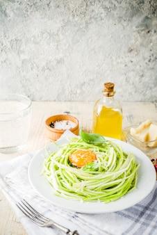 Модные веганские рецепты, спагетти из цуккини с сыром, яичным желтком с пармезаном, оливковым маслом и листьями базилика, легкая бетонная поверхность