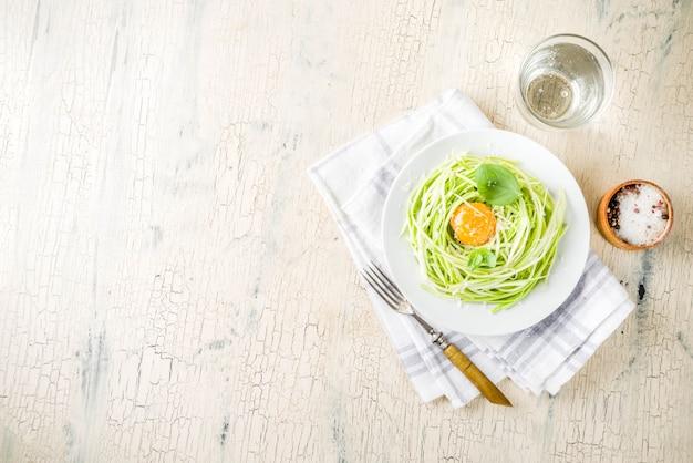Модные веганские рецепты, спагетти с цуккини, сыром, яичным желтком, пармезаном, оливковым маслом и листьями базилика, светлый бетонный фон