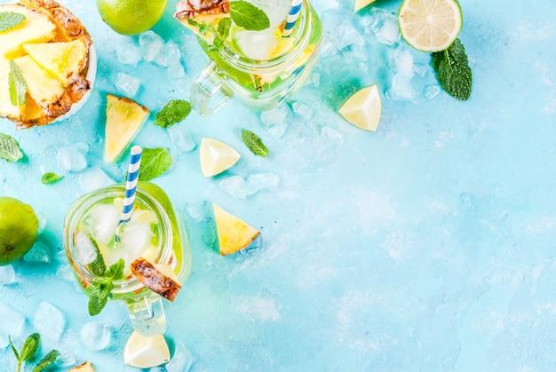 Тропический напиток ананасовый мохито или лимонад со свежим лаймом и мятой светло-голубого фона