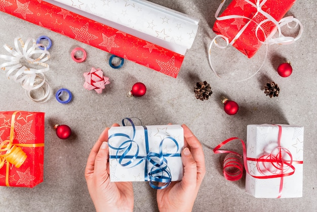 クリスマス休暇の準備。テーブルの上の贈り物や装飾品、写真の女の子の手には贈り物の一つが入っています。上面図
