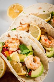 シーフードメキシコ料理トルティーヤタコス、伝統的な自家製サルササラダパセリ、新鮮なレモンアボカド、海老のポーンのグリル