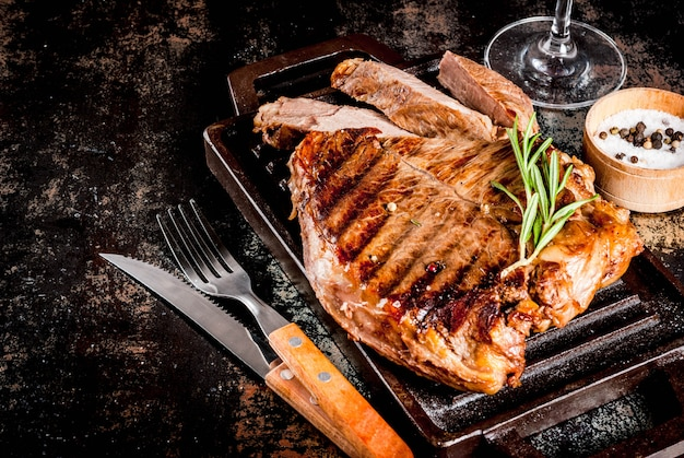 グリル鍋ボードにスパイスと牛肉のグリルステーキ、赤ワイングラス。コピースペース