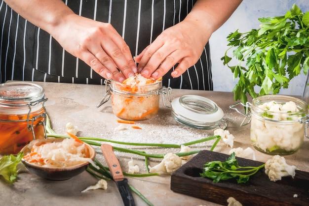 発酵食事の概念。ホーム缶詰とビレット。ビーガンフード野菜。ザウアークラウトを調理する人女性。保護、ブロッコリー、ニンジン、緑、玉ねぎの缶。