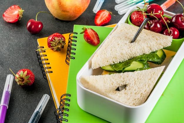 学校に戻る。箱に入った心のこもった健康的な給食:野菜とチーズのサンドイッチ、果実とリンゴ(リンゴ)、ノートブック、黒いテーブルの上の色付きペン。