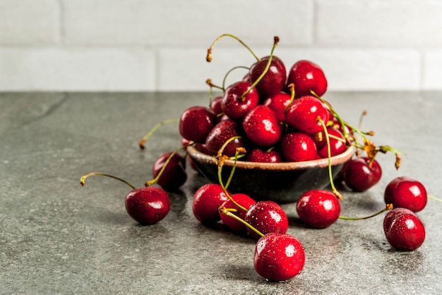 新鮮な生の有機季節のフルーツ。暗い石のテーブルの上に水滴の桜。コピースペース