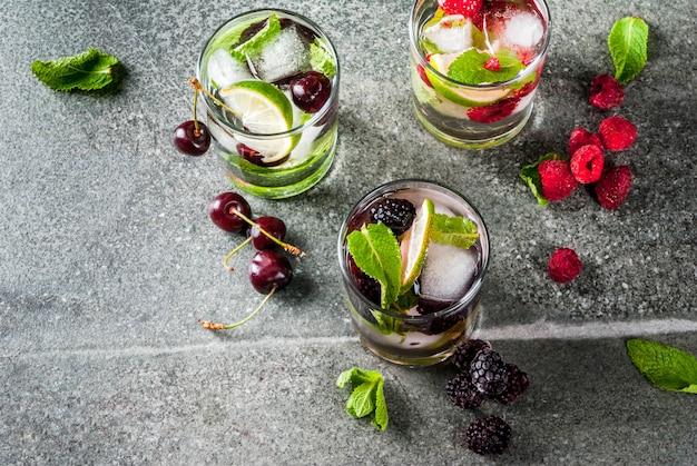 伝統的な夏の爽やかなドリンクベリーモヒートのセット。ライム、ミントの葉、ブラックベリー、ラズベリー、チェリー。暗い石のテーブルに食材を入れて。コピースペース