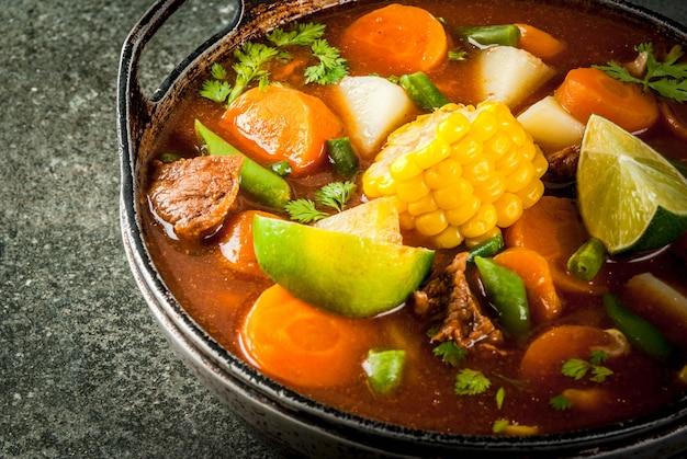 Традиционный мексиканский овощной суп с мясом, картофелем, морковью, фасолью, кукурузой и лаймом