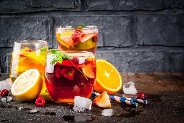 Летний холодный коктейль из трех фруктово-ягодных сангрийских напитков. красный белый розовый с яблоком, лимоном, апельсинами и малиной. темный фон
