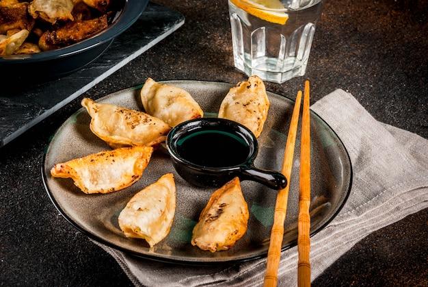 Жареные азиатские пельмени гёза на темной тарелке с палочками для еды и соевым соусом