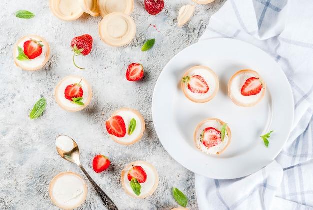 Летний сладкий домашний десерт мини чизкейки с клубникой на сером каменном столе