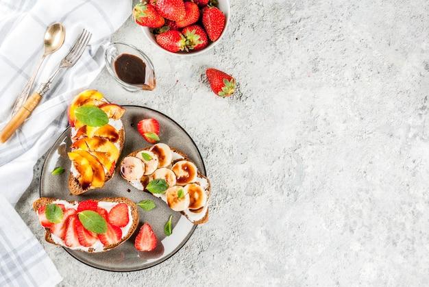 健康的な夏の朝食スナックフルーツとベリーのライ麦トーストサンドイッチ-ストロベリーピーチバナナ