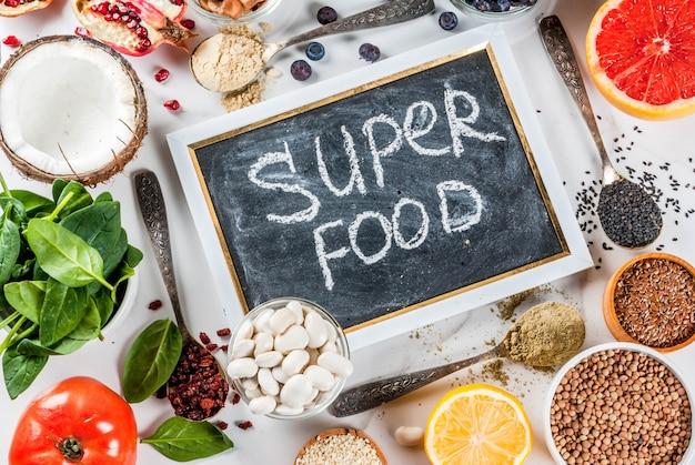 Набор органических здоровой диеты суперпродуктов - бобы бобовые орехи семена зелень фрукты и овощи на белом фоне