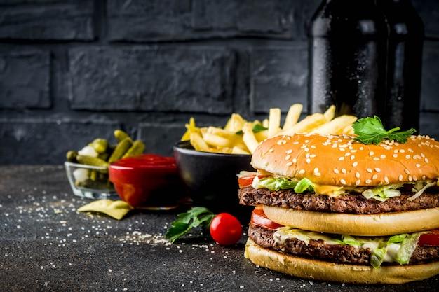 Различная партия еды гамбургеры картофель фри картофельные чипсы маринованные огурцы лук помидоры и холодные пивные бутылки ржавый черный бетонный фон