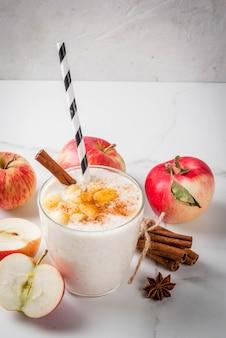 Здоровая веганская еда. диетический завтрак или закуска. смузи из яблочного пирога, с яблоками, йогуртом, корицей, специями, грецкими орехами. в стакане, на белом мраморном столе. копировать пространство