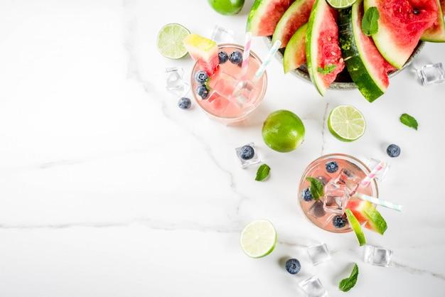 夏の飲み物、スイカ、ブルーベリーレモネードカクテル、ライム、ミント、アイスキューブ、白い大理石の背景