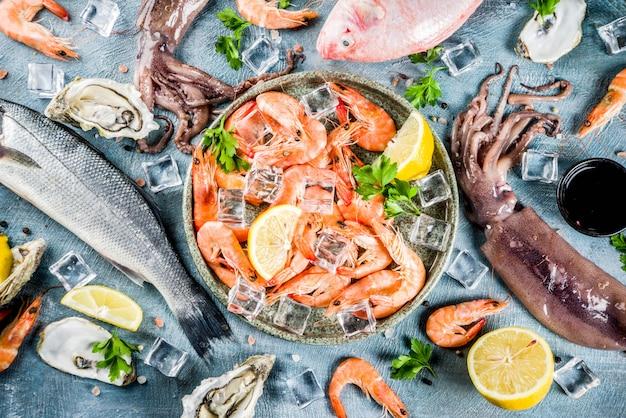 新鮮な生の魚介類イカエビカキムール貝の魚、明るい青の背景にハーブレモンのスパイス