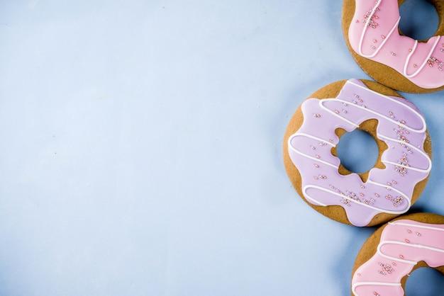 お菓子の創造的なレイアウト、ロリポップ、ゼリー、キャンディ、クッキードーナツ、カップケーキ、明るい青の背景とデザートのコンセプト