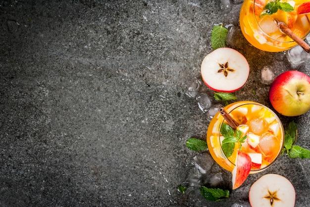 伝統的な秋の飲み物、ミント、シナモン、氷とアップルサイダーモヒートカクテル。黒い石のテーブルに、コピースペース平面図