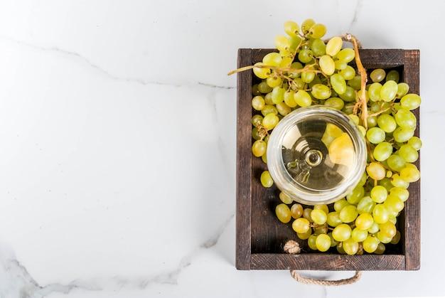 白ブドウと白い大理石のテーブルの上の木製トレイにガラスの白ワイン。コピースペーストップビュー