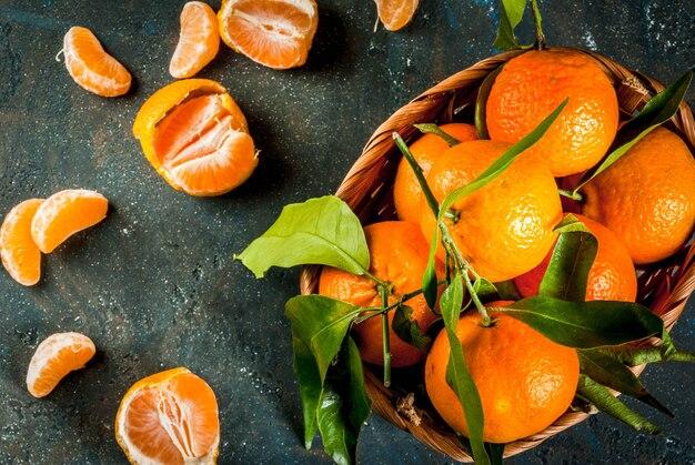 Свежие сырые органические мандарины с зелеными листьями в маленькой корзине на темном фоне бетонного камня, копией пространства