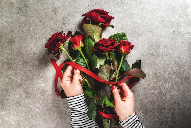 お祝い背景、バレンタインの日。少女(写真の手)は赤いバラの花束を作り、赤いリボンで結びます。