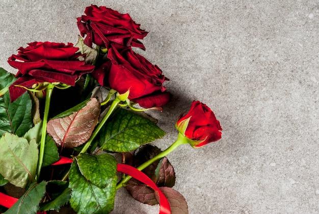 休日の背景、バレンタインの日。赤いバラの花束、赤いリボンとネクタイ、ラップされたギフトボックスと赤いろうそく。