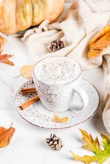 秋のホットドリンク。カボチャのラテ、ホイップクリーム、シナモン、アニス、白い大理石のテーブルの上にセーター(毛布)、紅葉、モミの実を添えて。コピースペース