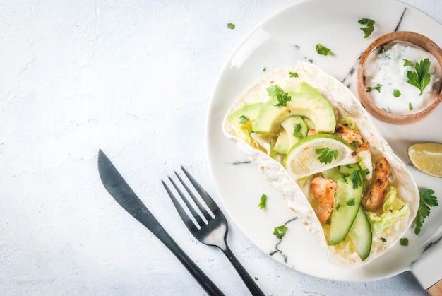 健康食品スナック。鶏のグリル、アボカド、新鮮なサルサ、レタス、ライムのトルティーヤタコス。ヨーグルトとパセリのソース。明るい灰色の石の大理石のテーブル、大理石のプレート。コピースペーストップビュー