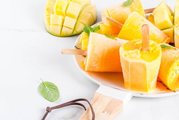 Замороженный коктейль из манго с листьями мяты и свежими фруктами манго