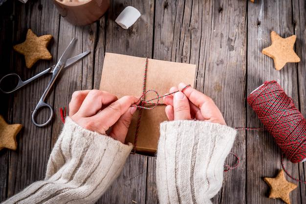 Подготовка к осенним и зимним праздникам. человек упаковывает печенье в подарок в поделку, новогоднюю ленточку, руки в рамке. деревенский старый стол, вид сверху копией пространства