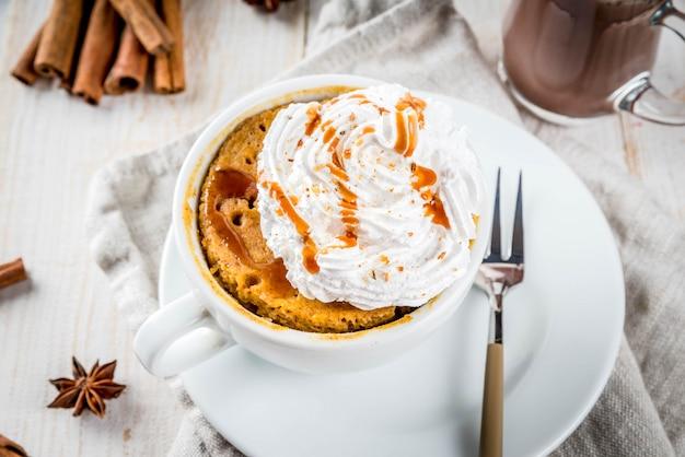 カボチャ、ファーストフード、電子レンジの食事のレシピ。ホイップクリーム、アイスクリーム、シナモン、アニス入りのマグカップのスパイシーなカボチャのパイ。ホットチョコレートのカップと白い木製のテーブル。コピースペース