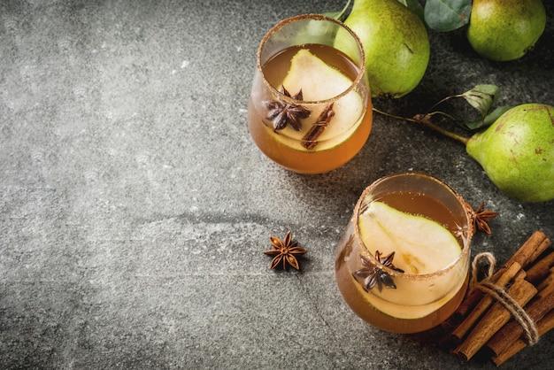 秋の飲み物。グリューワイン。ナシ、サイダー、チョコレートシロップ、シナモン、アニス、ブラウンシュガーと伝統的な秋のスパイシーなカクテル。黒い石のテーブル。コピースペーストップビュー